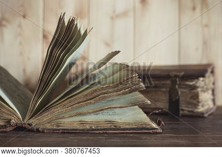 A Very Old Open Book With Yellowed Pages On Wooden Table. In The Background Is Second Book In Shabby