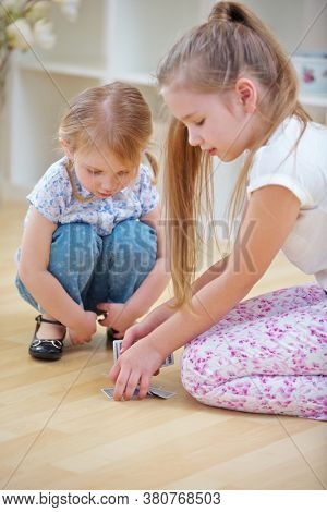 Two children shuffle cards on the floor before playing