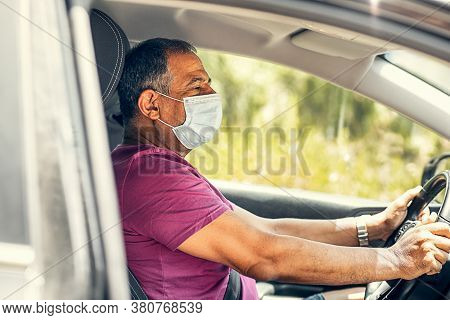 Senior Man In Protective Sterile Medical Mask Driving Car. The Concept Of Preventing The Spread Of T