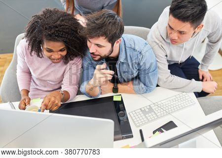 Web design team develops a design idea together on the computer in the office