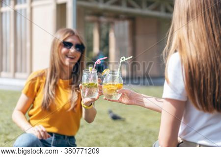 Two Beautiful Young Woman In The Summer Sunny City Drinking A Cocktail From Glass Jars. Sitting On G