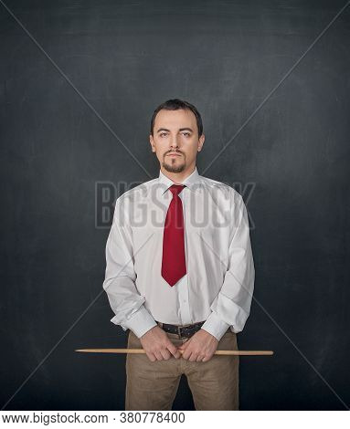 Serious Business Man Or Teacher With Pointer On Blackboard