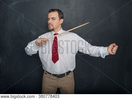 Serious Teacher With Pointer Writing Something On Blackboard Background
