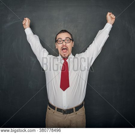 Successful Handsome Happy Man With Raising Arms On Chalkboard