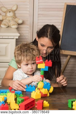 Mother And Son In Playroom On Light Wooden Background.