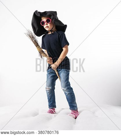A Little Boy In A Witch Hat Jumps On A Mattress And Flies On A Broomstick.