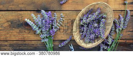 Bunch Of Lavender Flowers Next To A Little Basket Full Of Petals  Wooden Background