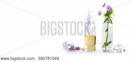 Front View Of Essential Oil And Petals Of Flowers In Bottle In Panoramic Size On White Background