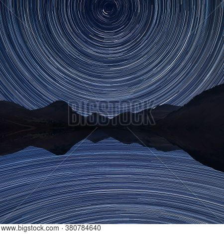 Digital Composite Image Of Star Trails Around Polaris With Stunning Landscape Of Mountains In Lake D