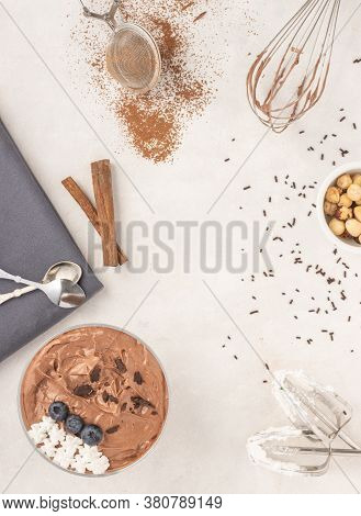Chocolate Mousse Dessert Placed On White Background With Hazelnuts, Dark Chocolate, Blueberries, Top
