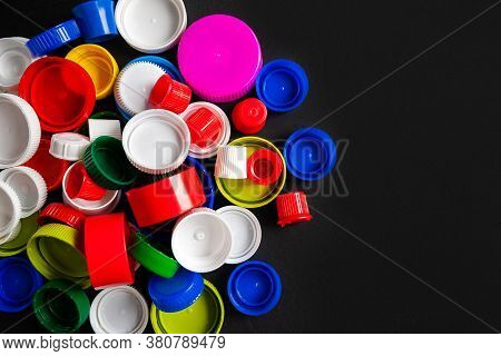 Top View Of A Pile Of Plastic Bottle Caps On A Black Background With Copy Space. Recycled Plastic Bo
