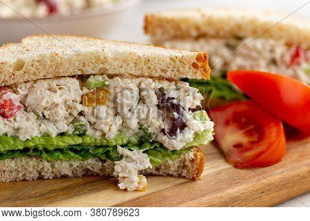 Closeup Of Chicken Salad Sandwich With Lettuce On Whole Wheat Bread Cut In Half On A Wooden Board