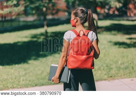 Student wearing mask on campus going back to school. Girl university student wearing protective face covering walking with books and backpack. Young woman at College.