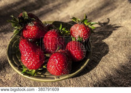 Plate Of Ripe Strawberries On A Wooden Background. Shot With Harsh Sunlight. Summer Background
