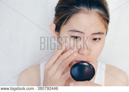 Portrait Of Asian Woman Worry About Her Face When She Saw The Problem Of Acne And Scar By The Mini M
