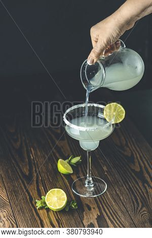 Woman Hands Is Pouring Margarita Cocktail With Lime And Ice On Dark Wooden Background, Copy Space. C