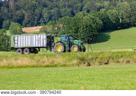 Bavaria/ Germany - August 07,2020: John Deere 6175r Tractor Drives With A Fliegl Gigant Trailer On A