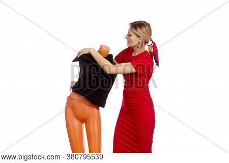 A Young Woman In A Red Dress Puts A Black Dress On A Mannequin
