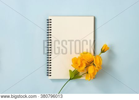 Spiral Notebook Or Spring Notebook In Unlined Type And Orange Flowers At Bottom Right On Blue Pastel