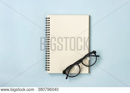 Spiral Notebook Or Spring Notebook In Unlined Type And Eyeglasses On Blue Pastel Minimalist Backgrou