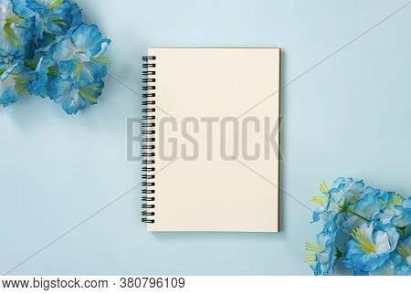 Spiral Notebook Or Spring Notebook In Unlined Type And Blue Flowers At Bottom Right And Top Left Cor