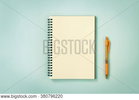 Spiral Notebook Or Spring Notebook In Unlined Type And Orange Pen On Blue Pastel Minimalist Backgrou