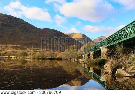 Railway Bridge Over Lock Awe, Scotland With A Clear Reflection Leading Into The Scottish Mountains.