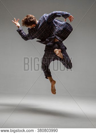 Stylish Guy Dancer Levitating Isolated On Gray Background. Dance School Poster. Back View. Photograp