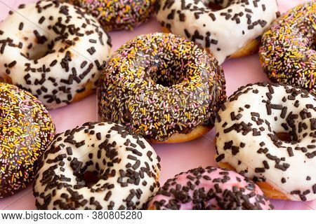 Close Up View Of Delicious Colourful Donuts With Sprinkles And Chocolate Flakes . Assorted Donuts Wi