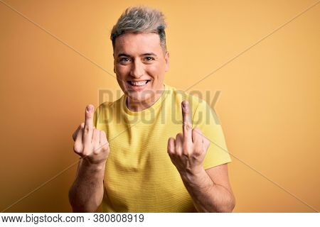 Young handsome modern man wearing yellow shirt over yellow isolated background Showing middle finger doing fuck you bad expression, provocation and rude attitude. Screaming excited
