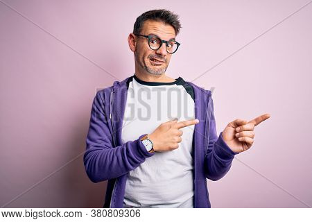 Young handsome man wearing purple sweatshirt and glasses standing over pink background Pointing aside worried and nervous with both hands, concerned and surprised expression