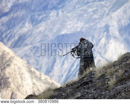 Hunter Standing On The Mountainside Shoots A Rifle With His Hands. The Shooter Aims At The Optical S