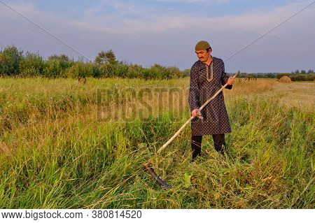 An Senior Muslim Man In A Skullcap And Traditional Clothes Mows Hand-scythe Grass In A Hayfield. Cou