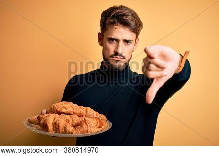 Young man with beard holding plate with croissants standing over isolated yellow background with angry face, negative sign showing dislike with thumbs down, rejection concept