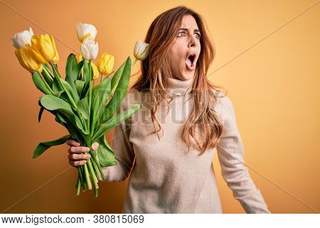 Young beautiful brunette woman holding bouquet of yellow tulips over isolated background angry and mad screaming frustrated and furious, shouting with anger. Rage and aggressive concept.