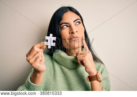 Young beautiful hispanic woman holding puzzle piece as cooperation solution on business serious face thinking about question, very confused idea