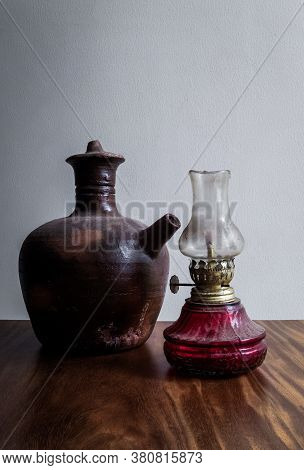 Traditional Water Jug Made By Clay And Traditional Oil Lamp On A Wooden Table