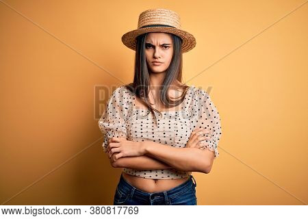 Young beautiful brunette woman wearing t-shirt and summer hat over yellow background skeptic and nervous, disapproving expression on face with crossed arms. Negative person.