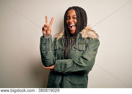 Young african american woman wearing winter parka coat over isolated background smiling with happy face winking at the camera doing victory sign. Number two.