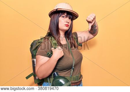 Young plus size woman wearing explorer hat and backpack with angry face, negative sign showing dislike with thumbs down, rejection concept