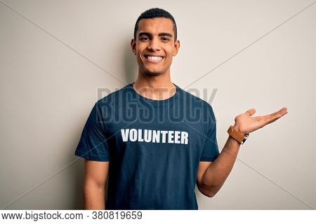 Young handsome african american man volunteering wearing t-shirt with volunteer message smiling cheerful presenting and pointing with palm of hand looking at the camera.