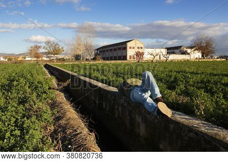 Man Lying Down And Sleeping Relaxed In A Ditch Wall.