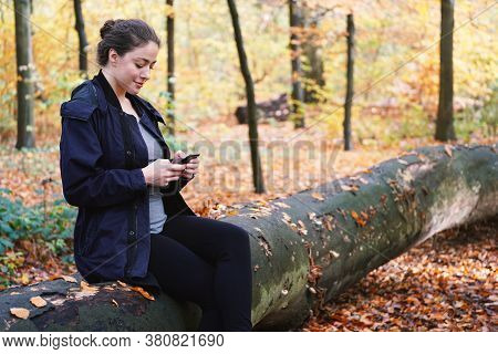 Young Woman In Her 20s Using Mobile Smartphone While Resting Outdoors In Woods