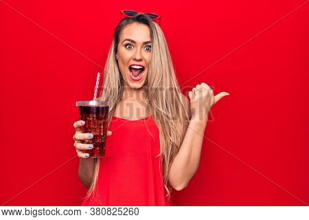 Beautiful blonde woman drinking cola beverage refreshment using straw over red background pointing thumb up to the side smiling happy with open mouth