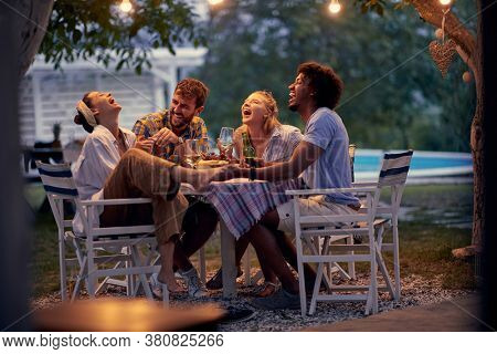 Group of cheerful friends having  at party.Young people having fun at a dinner party,