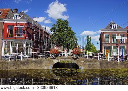 Delft, The Netherlands - August 5, 2020: View On A Bridge And Channel In The City Center Of Delft.