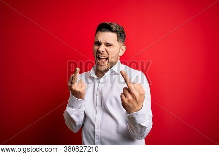 Young business man with blue eyes wearing elegant shirt standing over red isolated background Showing middle finger doing fuck you bad expression, provocation and rude attitude. Screaming excited