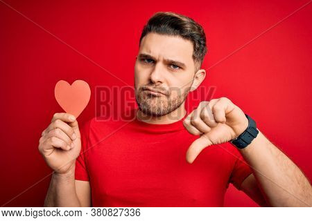 Young romantic man with blue eyes holding red heart paper shaped over red background with angry face, negative sign showing dislike with thumbs down, rejection concept