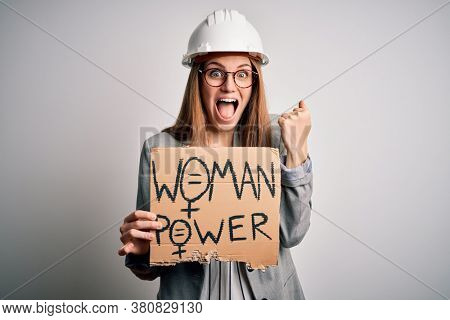 Young redhead architect asking for women rights holding banner with woman power message screaming proud and celebrating victory and success very excited, cheering emotion