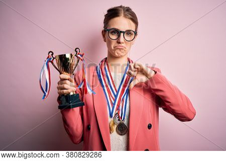 Young beautiful redhead woman holding trophy wearing medals over pink background with angry face, negative sign showing dislike with thumbs down, rejection concept